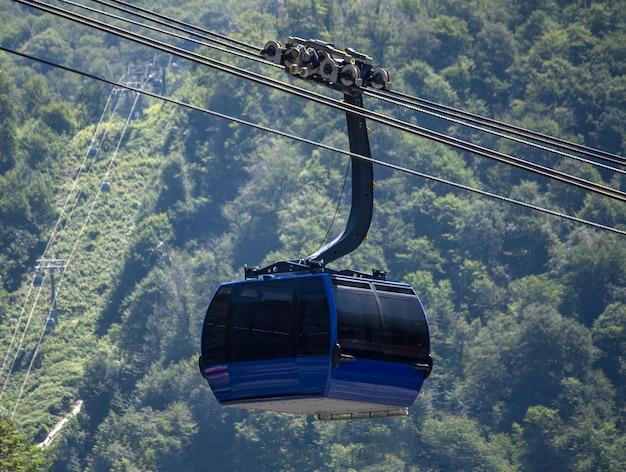 산속의 숲 배경에 있는 케이블카 택시, 산에서 운송