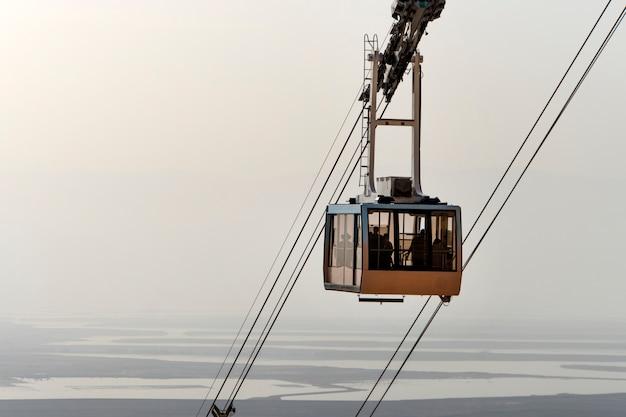 ケーブルカーは観光客をマサダの山の要塞に持ち上げます。ジュダイアン砂漠、死海、曇り空を背景にケーブルカー。砂漠の美しい風景。