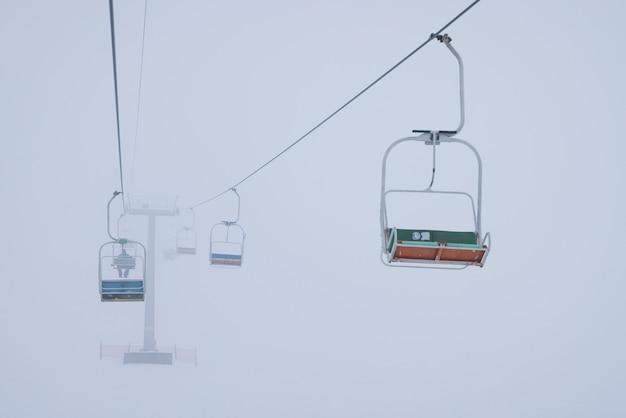 ケーブルカーは霧の空を背景に静かなスキーリゾートのケーブルにぶら下がっています