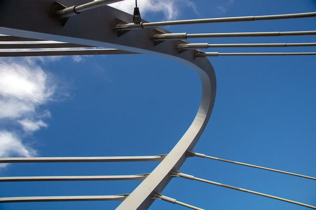 Cable-stayed bridge against the blue cloudy sky close-up on a sunny summer day