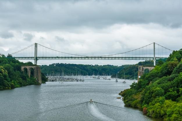 Вантовый мост в зеленом естественном лесу, с драматическим облачным небом. моторная лодка плывет по реке
