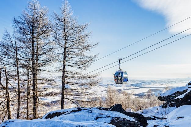 카바나가 있는 케이블카 또는 케이블카는 겨울날 산으로 올라가고 배경에는 푸른 하늘