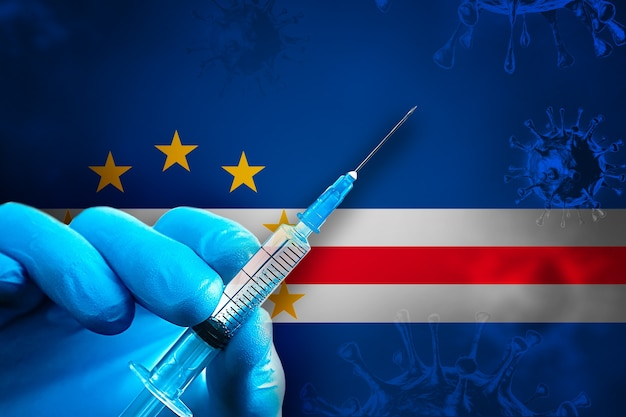 카보 베르데 코비드19 예방 접종 캠페인 파란색 고무 장갑을 끼고 깃발 앞에 주사기를 들고 있습니다