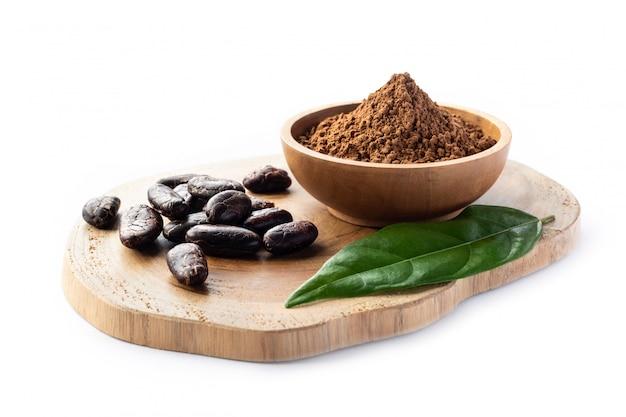 カカオ豆と白で隔離される木製のボウルにパウダー。