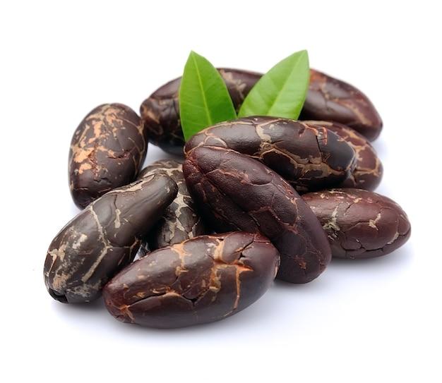 Какао-бобы с изолированными листьями.