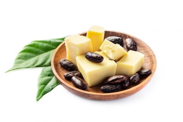 カカオバターと白で隔離される木製のボウルに豆。