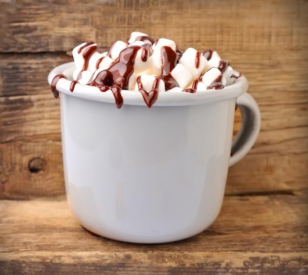 Напиток какао с зефиром и шоколадной начинкой на деревянном столе.