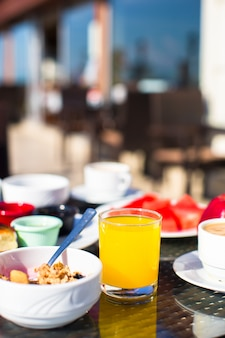 Cacao, juice, muesli and fruits for breakfast at a cafe in the resort