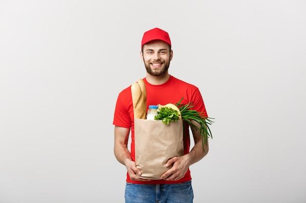 Концепция доставки - красивый cacasian доставщик, перевозящих пакет мешок продуктов питания и напитков из магазина. изолированный на серой стене студии. копировать пространство.