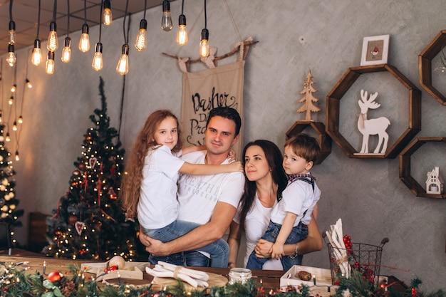 Счастливая семья cacasian на уютном доме отдыха украшенном в светах рождества. веселые дети и родители отмечают традиционные праздники
