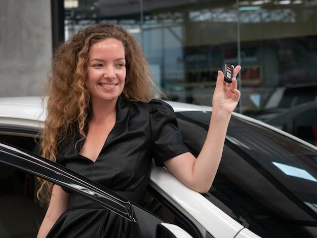 カカオの女性が車の近くに立って、車のキーを示します。
