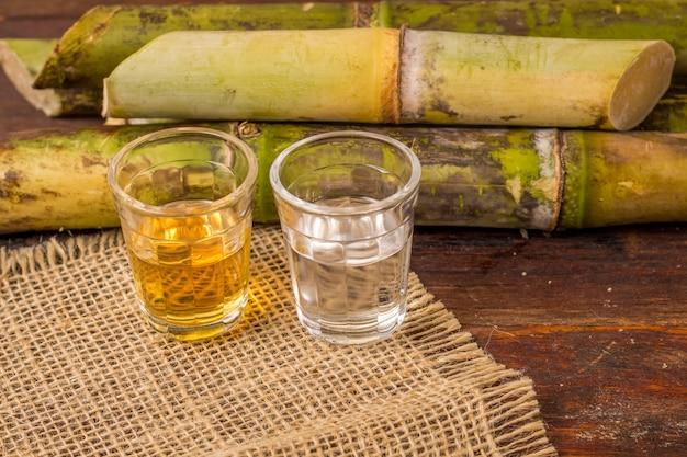 Cachaca - это название типичного алкогольного напитка, производимого в бразилии с сахарным тростником. традиционный напиток из бразилии на деревянном столе