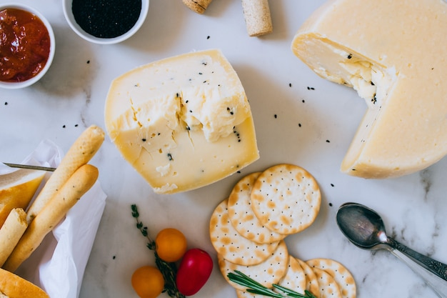 Cachotta cheese with black cumin, jam, baguette, crackers, rosemary and thyme on marble