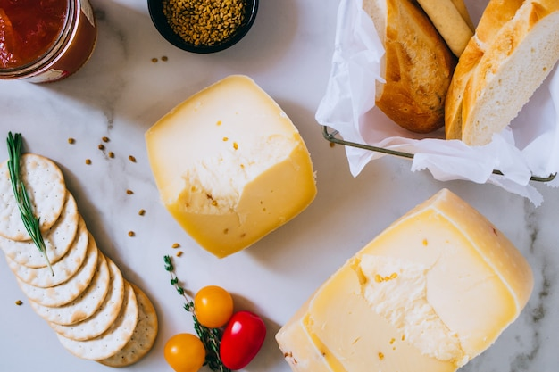 Cachotta cheese with with fenugreek, jam, baguette, crackers, rosemary and thyme on marble