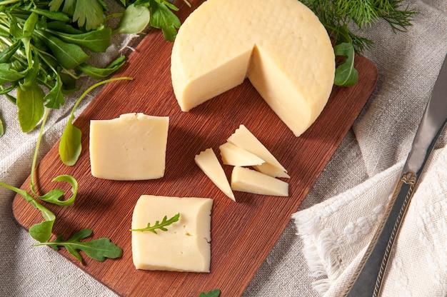 カシオッタチーズはスライスされています。長方形の木の板の上。ルッコラ、パセリ、コリアンダーで飾られています。背景の灰色のリネン生地。上からの眺め。