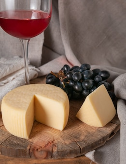 둥근 나무 판자에 카시오타 치즈. 슬라이스 치즈, 검은 포도, 레드 와인 한 잔 옆. 리넨으로 만든 배경 회색 패브릭.