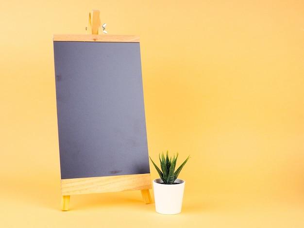 あなたのテキストのためのサボテンと黒板、ミニマリストスタイル、黒いフレームのモックアップの背景
