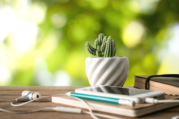 Cactus flower notebook, pencil and smartphone on wood table with nature background.