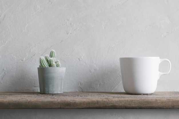 Cactus flower with white coffee cup on wood wall shelves modern interior background .