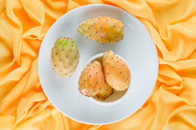 Плоды кактуса в миске и тарелке на желтой текстильной поверхности