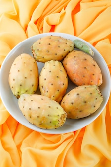 Cactus fruits in a white plate on yellow textile surface