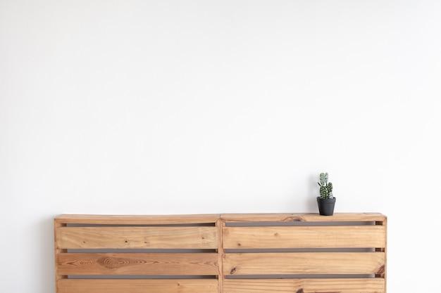 Модель кактуса на паллетной доске с белой стеной.