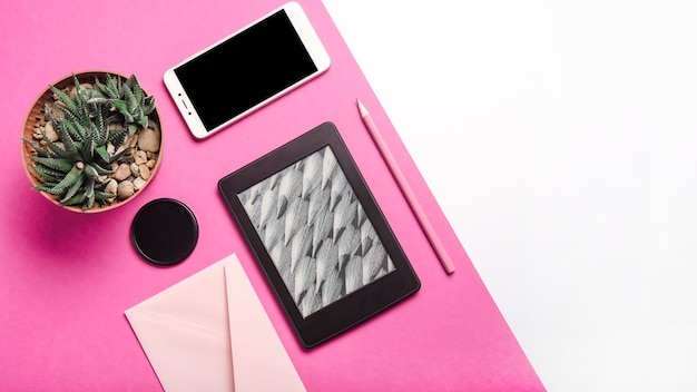 Cactus pot plant; mobile phone; ebook reader; pencil; envelope on dual pink and white background