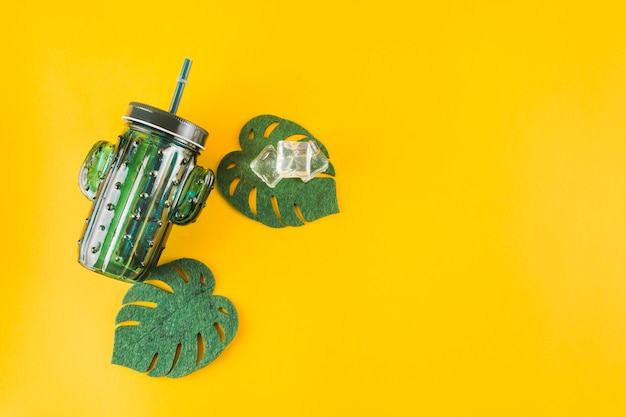 Cactus shape jar with ice cubes and artificial monstera leaves on yellow background