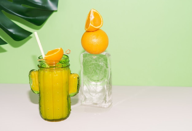 Cactus shaped glass with orange juice with fruit decoration on ice block. copy space.