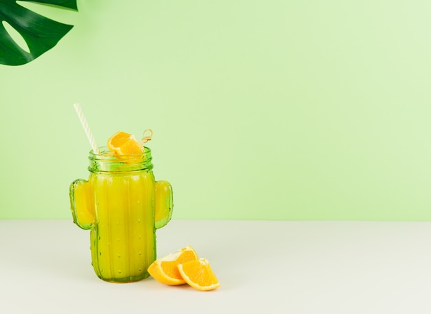 Cactus shaped glass with orange juice with green background. copy space.