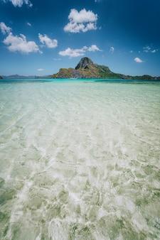 전경에서 파란색 얕은 라군과 cadlao 섬. 엘니도, 팔라완, 필리핀.