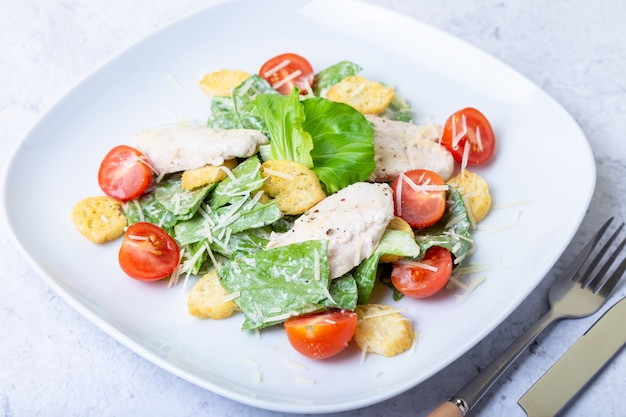 Caesar (cesar) salad with chicken, crackers, parmesan and cherry tomatoes. close-up.