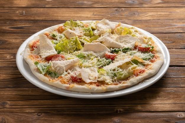 木製のキッチンテーブルの白いセラミックプレートに鶏の胸肉、レタス、チェリートマト、パルメザンチーズを添えた薄い生地のシーザーピザ。