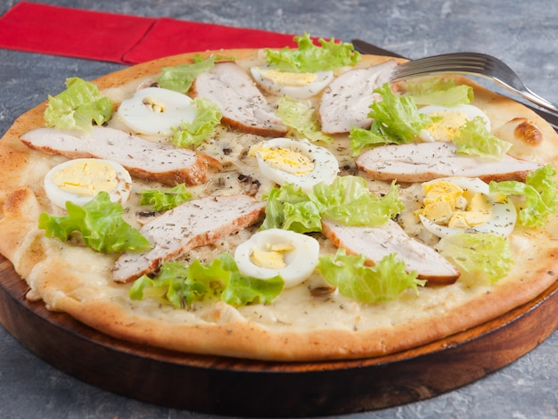Caesar pizza with smoked chicken breast chicken egg and mushrooms