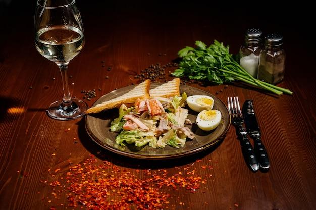 Caesar salad on black plate on wooden table