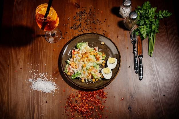 Caesar salad on black plate on wooden table.