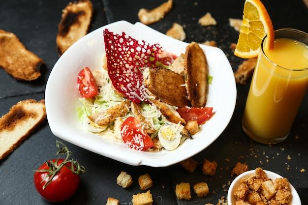 Vista laterale del cocktail delle acciughe del parmigiano del limone del pomodoro della lattuga del pollo dell'insalata di caesar