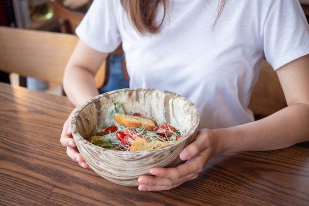Салат цезарь держится в руках молодых женщин. выбор еды фруктов и овощей в определенных приемах пищи.