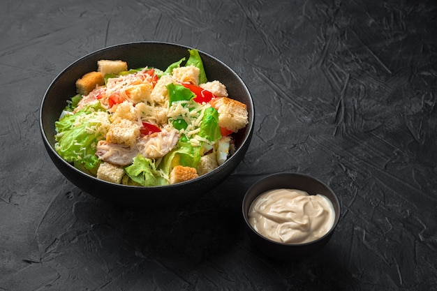 검정색 배경에 소스와 함께 블랙 세라믹 접시에 시저 샐러드. 복사 할 공간이있는 요리 배경.