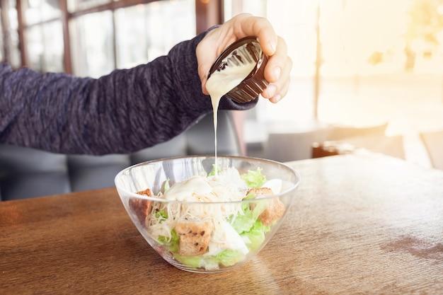 Салат цезарь в стеклянной тарелке. салат с жареной курицей, зеленым салатом, тостами, соусом, помидорами, сыром