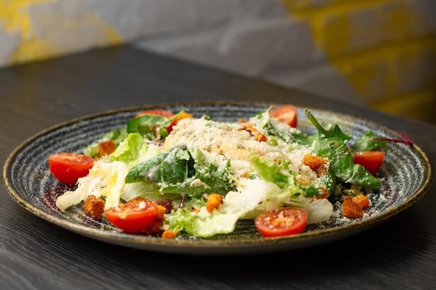 Салат цезарь, в темной глиняной тарелке на деревянном столе
