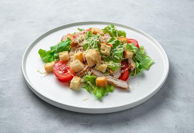 회색 배경에 평평한 접시에 시저 샐러드. 최소한의 요리 배경. 측면보기, 클로즈업.