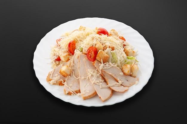 하얀 접시에 시저 샐러드입니다. 치킨 필레, 방울 토마토, 샐러드 믹스, 크루통, 파마산 치즈, 소스. 어두운 배경입니다. 외딴. 확대.