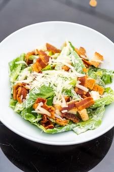 Салат цезарь на белой тарелке