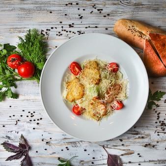 Insalata caesar in un piatto con pomodoro, pane, erbe e spezie