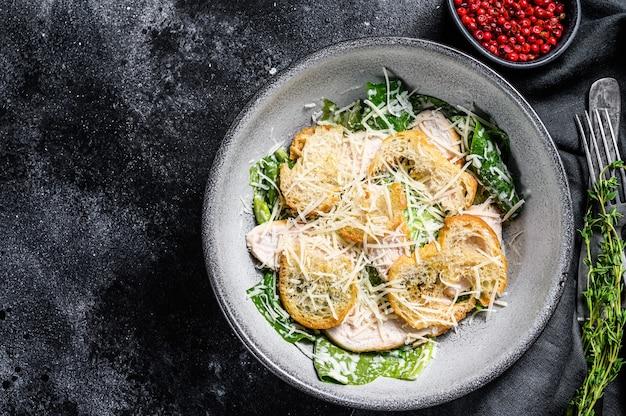 Салат цезарь с сыром пармезан, печенье коста. здоровая пища. черный фон.