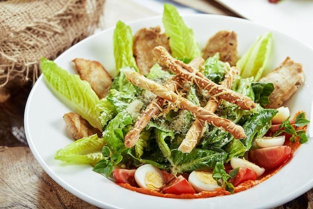 Салат цезарь с хлебными палочками, перепелиными яйцами, помидорами черри и жареным цыпленком в тарелке на белом фоне.