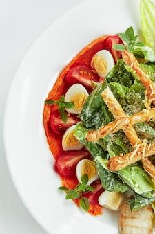 Салат цезарь с хлебными палочками, перепелиными яйцами, помидорами черри и курицей-гриль в тарелке на белой поверхности