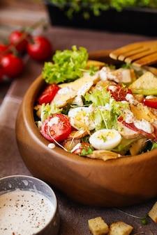Салат цезарь с помидорами черри и перепелиными яйцами в деревянной миске