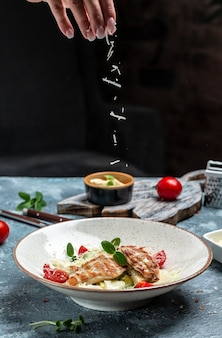 Caesar salad with chicken breast. female hand sprinkles parmesan cheese in a freeze motion, dark wooden background, cooking concept, vertical image. copy space.